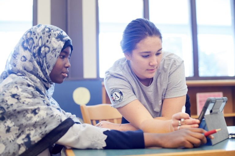 Student and AmeriCorps member work on laptop together