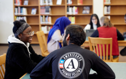 AmeriCorps volunteer talking with student in library