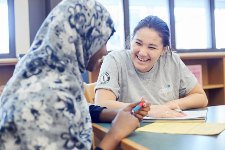 AmeriCorps member laughing with female student